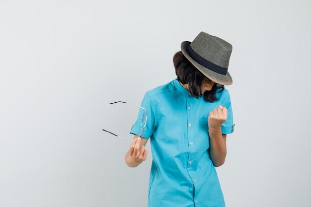 Młoda dama pokazuje gest zwycięzcy, trzymając okulary w niebieskiej koszuli, kapeluszu