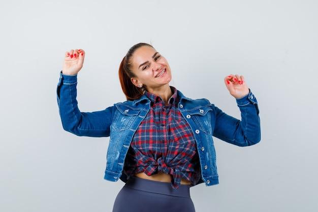 Młoda dama pokazuje gest zwycięzcy w koszuli, kurtce i patrząc szczęśliwy, widok z przodu.