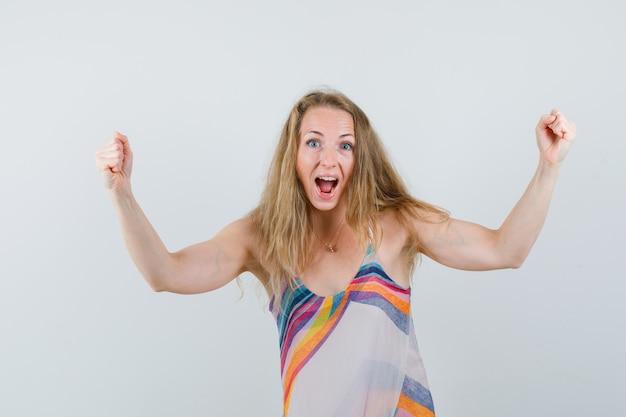 Młoda dama pokazuje gest zwycięzcy w letniej sukience i wygląda błogo