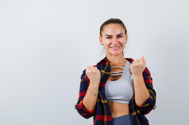 Młoda dama pokazuje gest zwycięzcy w top, koszulę w kratę i wygląda na szczęśliwą. przedni widok.