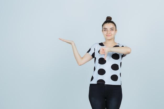 Młoda dama pokazuje kciuk w dół, udając, że trzyma coś w koszulce, dżinsach i wygląda pewnie. przedni widok.