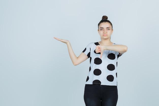 Młoda dama pokazuje kciuk w dół, udając, że trzyma coś w t-shircie, dżinsach i wygląda na niezadowoloną, widok z przodu.