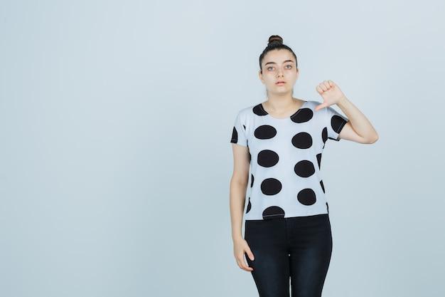 Młoda dama pokazuje kciuk w dół w koszulce, dżinsach i wygląda pewnie, widok z przodu.