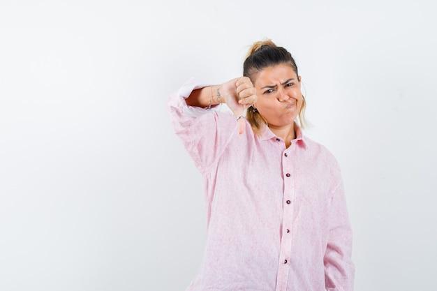 Młoda dama pokazuje kciuk w dół w różowej koszuli i wygląda na niezadowolonego