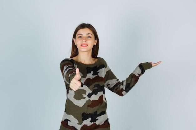 Młoda dama pokazuje kciuk w górę, udając, że pokazuje coś w swetrze