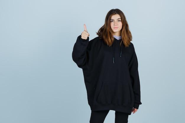 Młoda dama pokazuje kciuk w górę w dużej bluzie z kapturem, spodniach i wygląda błogo, widok z przodu.