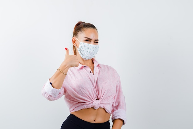 Młoda dama pokazuje kciuk w koszuli, spodniach, masce i wygląda wesoło