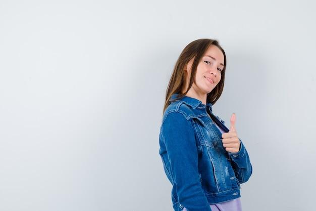 Młoda dama pokazuje kciuk w t-shirt, kurtkę i wyglądający pewnie.