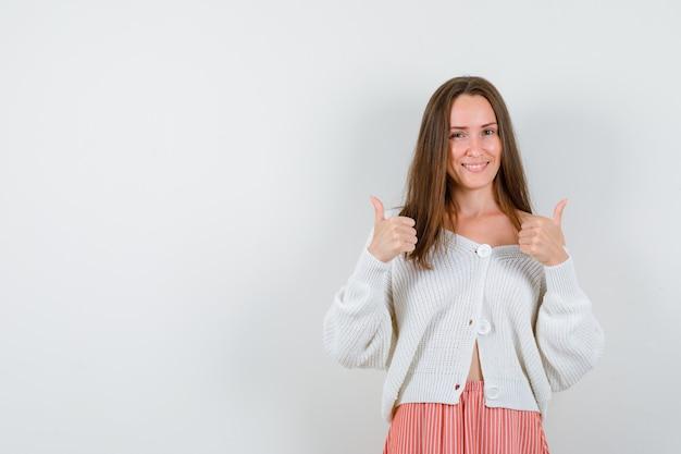 Młoda dama pokazuje kciuki do góry w swetrze i spódnicy, patrząc szczęśliwy na białym tle