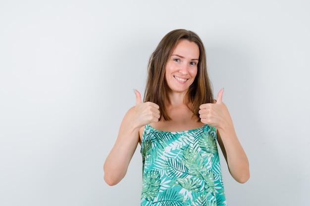 Młoda dama pokazuje kciuki w bluzce i wygląda na szczęśliwą. przedni widok.