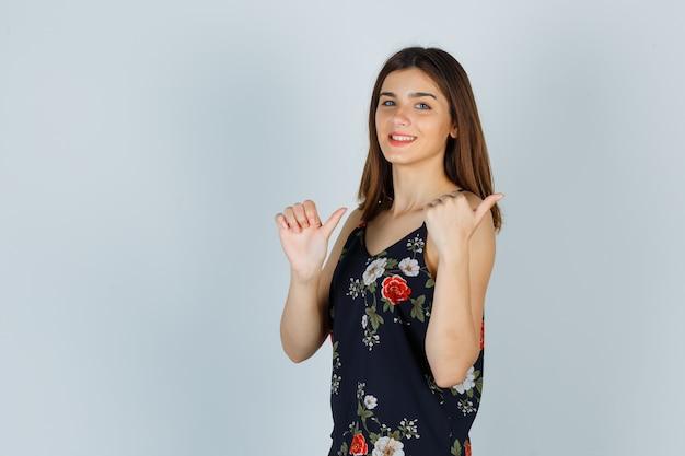 Młoda dama pokazuje kciuki w górę w kwiatowy top i wygląda na zadowoloną