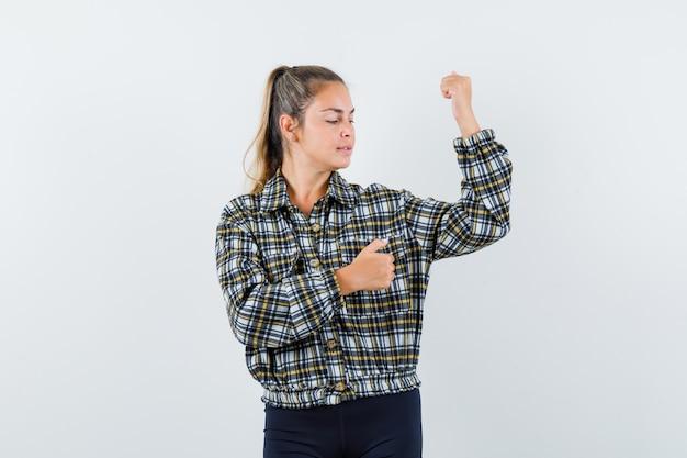 Młoda dama pokazuje mięśnie ramion w koszuli, spodenkach i wygląda pewnie. przedni widok.