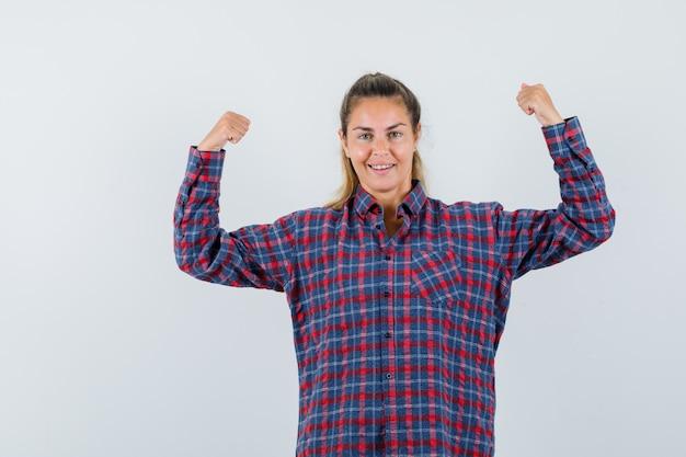 Młoda dama pokazuje mięśnie ramion w koszuli w kratę i wygląda pewnie, widok z przodu.