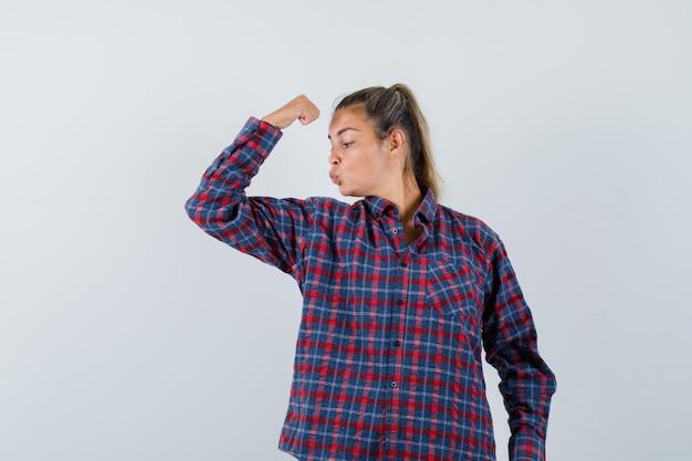Młoda dama pokazuje mięśnie ramion w kraciastej koszuli i wygląda pewnie. przedni widok.