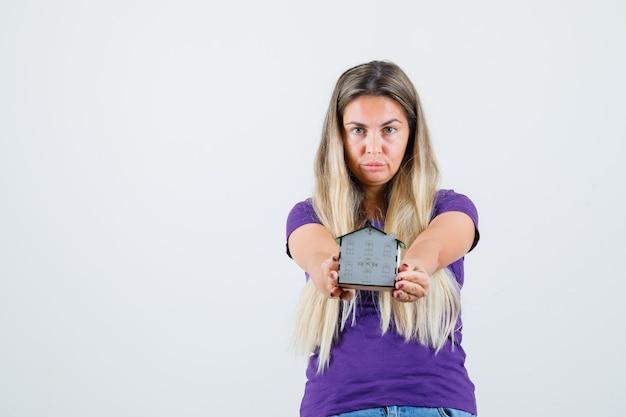 Młoda dama pokazuje model domu w fioletowej koszulce, widok z przodu.