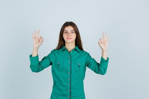 Młoda dama pokazuje ok gest w zielonej koszuli i wygląda pewnie, widok z przodu.