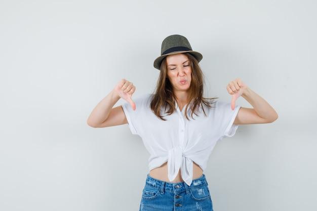 Młoda dama pokazuje podwójne kciuki w dół w koszulce, dżinsach, czapce i wygląda na niezadowoloną, widok z przodu.