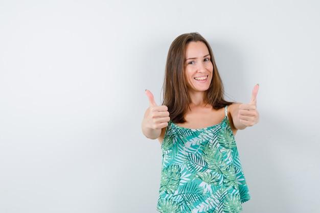 Młoda dama pokazuje podwójne kciuki w górę i wygląda na szczęśliwą. przedni widok.
