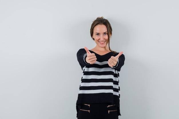 Młoda dama pokazuje podwójne kciuki w koszuli i wygląda wesoło