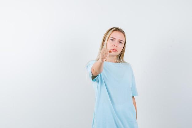 Młoda dama pokazuje zaciśniętą pięść w koszulce i wygląda poważnie. przedni widok.