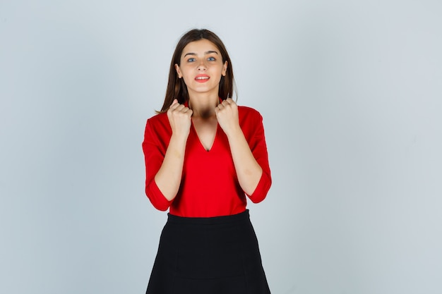 Młoda dama pokazuje zaciśnięte pięści w czerwonej bluzce, spódnicy i wyglądającej wesoło