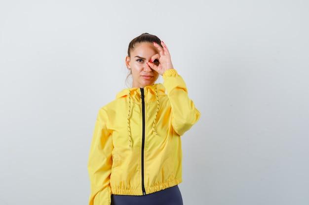 Młoda dama pokazuje znak ok na oku w żółtej kurtce i wygląda pewnie, widok z przodu.