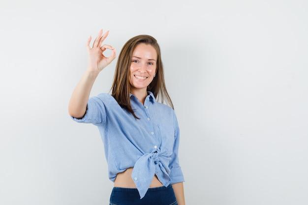 Młoda dama pokazuje znak ok w niebieskiej koszuli, spodniach i wygląda na zadowoloną.