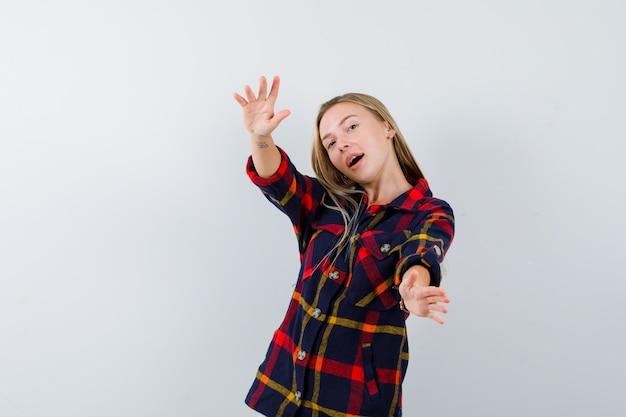 Młoda dama pokazuje znak rozmiaru w kraciastej koszuli i wygląda pozytywnie, widok z przodu.