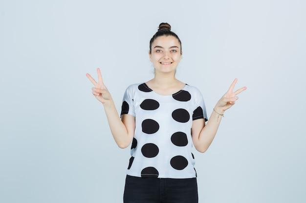 Młoda dama pokazuje znak zwycięstwa w koszulce, dżinsach i wygląda na szczęśliwą. przedni widok.