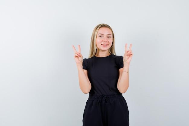 Młoda dama pokazuje znak zwycięstwa w koszulce, spodniach i wygląda na szczęśliwą, widok z przodu.