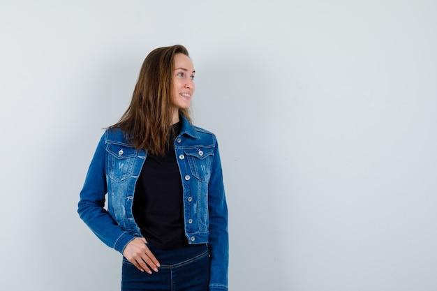 Młoda dama pozuje patrząc na bok w bluzce i wygląda atrakcyjnie. przedni widok.