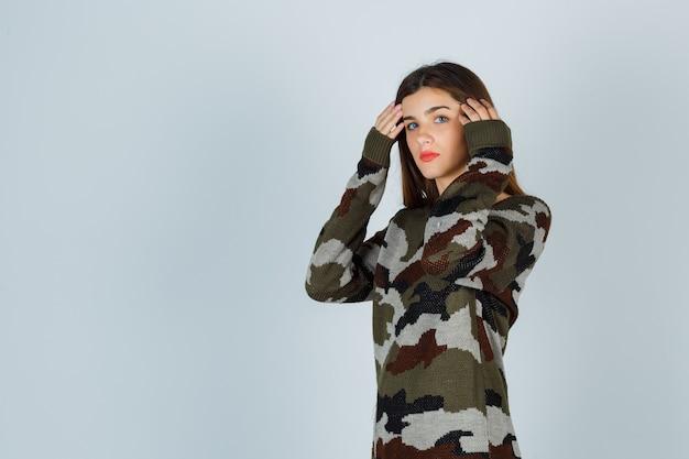 Młoda dama pozuje podczas układania włosów w sweter, spódnicę i wygląda pewnie