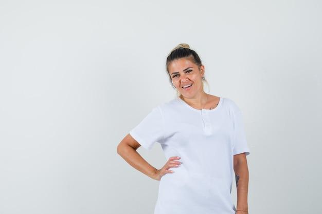 Młoda dama pozuje stojąc w koszulce i wyglądając pięknie