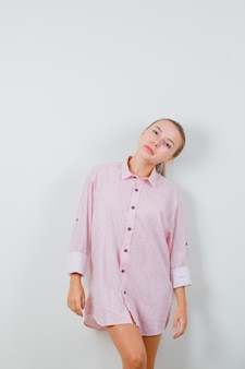 Młoda dama pozuje stojąc w różowej koszuli i wyglądając elegancko