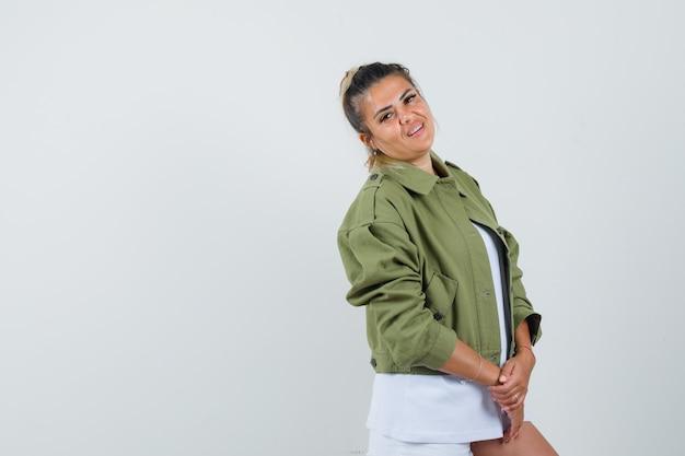 Młoda dama pozuje stojąc w spodenkach t-shirt i wyglądającej pięknie