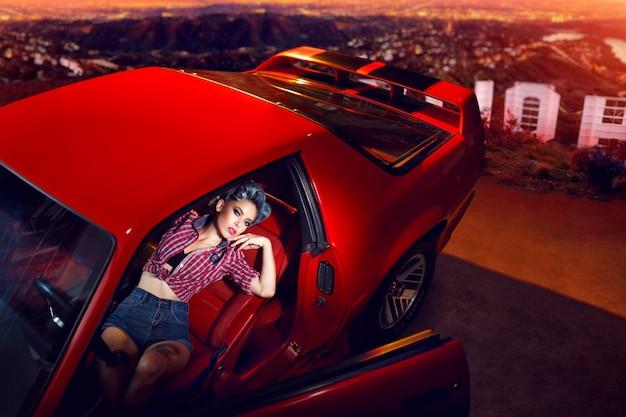 Młoda dama pozuje w czerwonym samochodzie