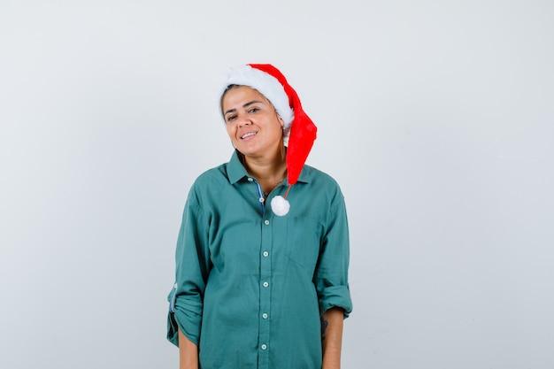 Młoda dama pozuje w świątecznym kapeluszu, koszuli i wygląda wesoło, widok z przodu.