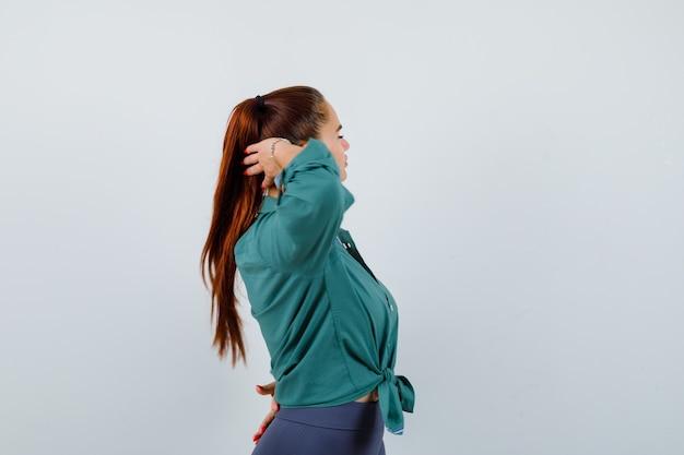 Młoda dama pozuje z głową za głową w zielonej koszuli i wygląda uroczo.