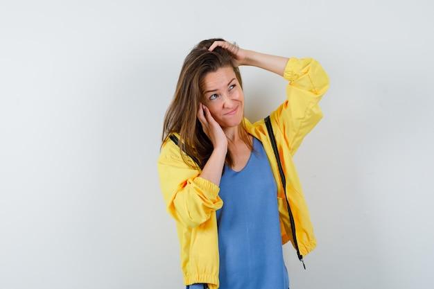Młoda dama pozuje z ręką na głowie w koszulce, kurtce i niepewnie