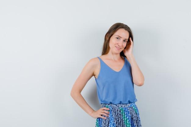 Młoda dama pozuje z ręką na głowie w niebieskiej bluzce, spódnicy i pięknie wygląda. przedni widok. miejsce na tekst