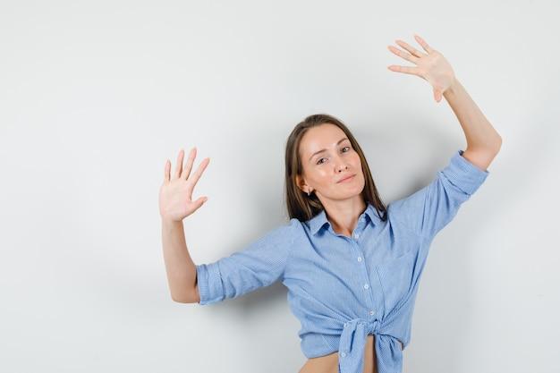 Młoda dama pozuje z uniesionymi dłońmi w niebieskiej koszuli i wygląda optymistycznie