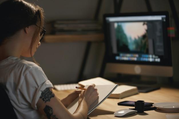 Młoda dama projektant siedzi w pomieszczeniu w nocy, rysując szkice