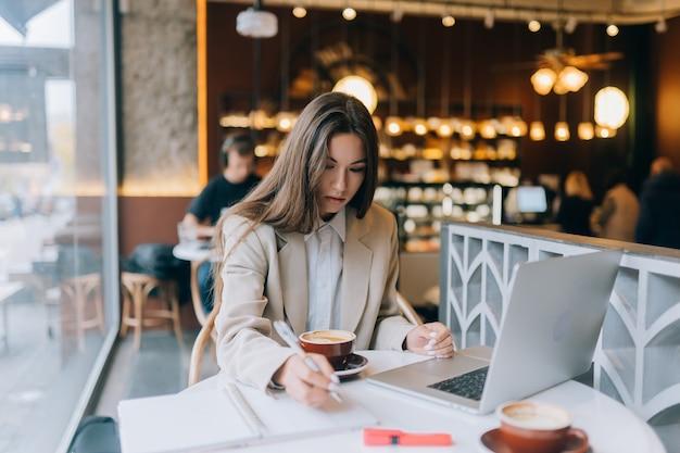 Młoda dama przeglądająca internet w kawiarni