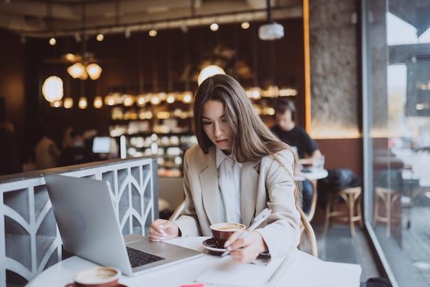 Młoda dama przeglądania internetu w kawiarni