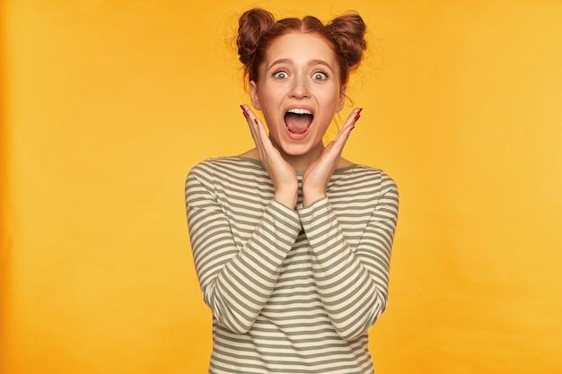 Młoda dama, przerażona ruda kobieta z dwoma bułeczkami. pokazuje, jak bardzo się bała tego, co widzi. sobie sweter w paski i krzyki odizolowane na żółtej ścianie