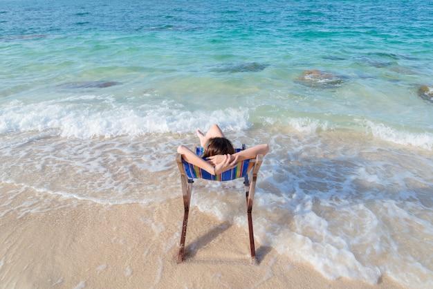 Młoda dama relaksuje w krześle na plaży przy słonecznym dniem
