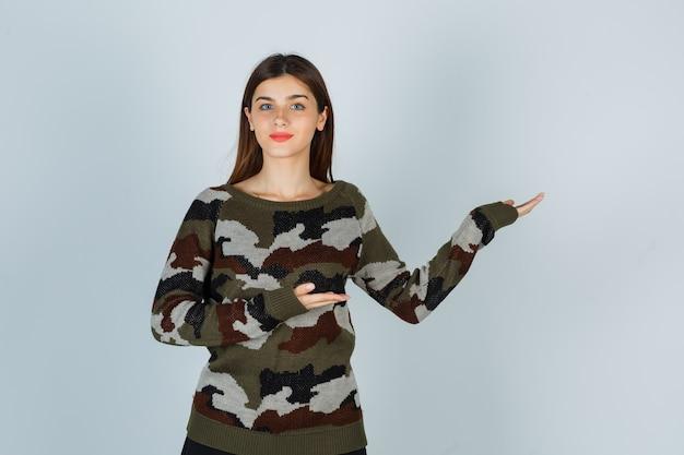 Młoda dama robi gest powitalny w swetrze, spódnicy i wygląda na zadowoloną