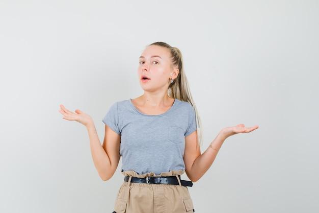 Młoda dama robi gest wagi w koszulce i spodniach i wygląda na zdezorientowanego