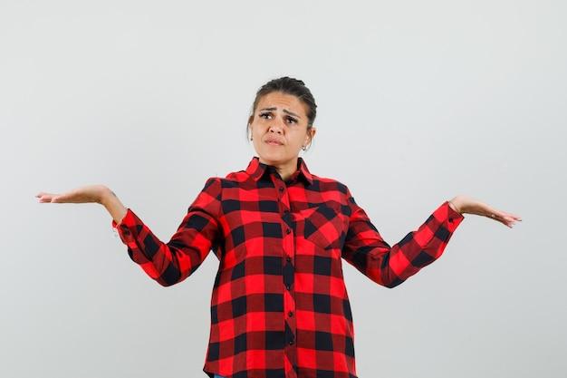 Młoda dama robi gest wagi w kraciastej koszuli i wygląda na zdezorientowanego.
