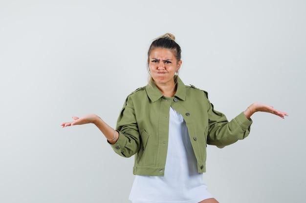 Młoda dama robi gest wagi w kurtce t-shirt i wygląda na zdezorientowanego